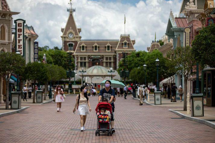 Grímuklæddir gestir Disneyland-skemmtigarðsins í Hong Kong. Honum verður lokað frá og með morgundeginum vegna fjölgunar nýrra smita í borgríkinu.