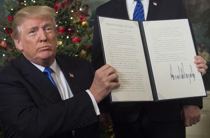 Trump var stoltur af undirskrift sinni í dag. Hann hefur neitað að opinbera skattaskýrslu sína og því liggur ekki fyrir hvaða áhrif nýju lögin hafa á skattgreiðslur hans.