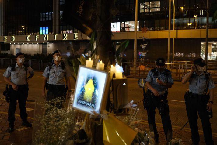Lögreglumenn í Hong Kong standa vakt við minningarskjöld um mótmælandann.