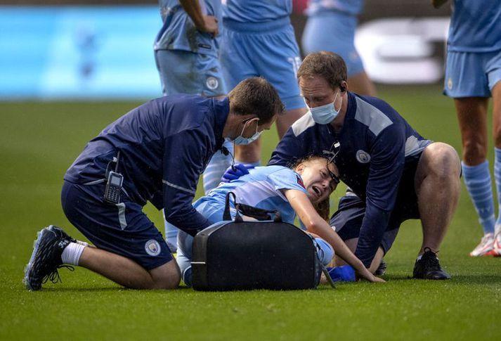 Læknar Manchester City huga að Esme Morgan sem liggur sárþjáð á grasinu.