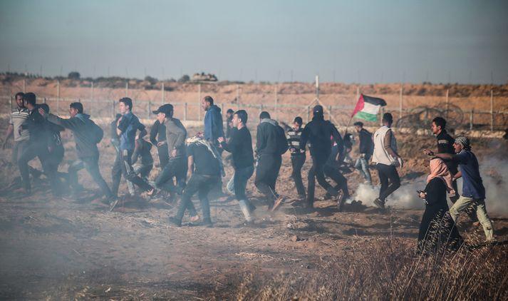 Mótmælendur á Gaza flýja táragas sem beitt var gegn þeim við landamæri Ísraels á föstudaginn.