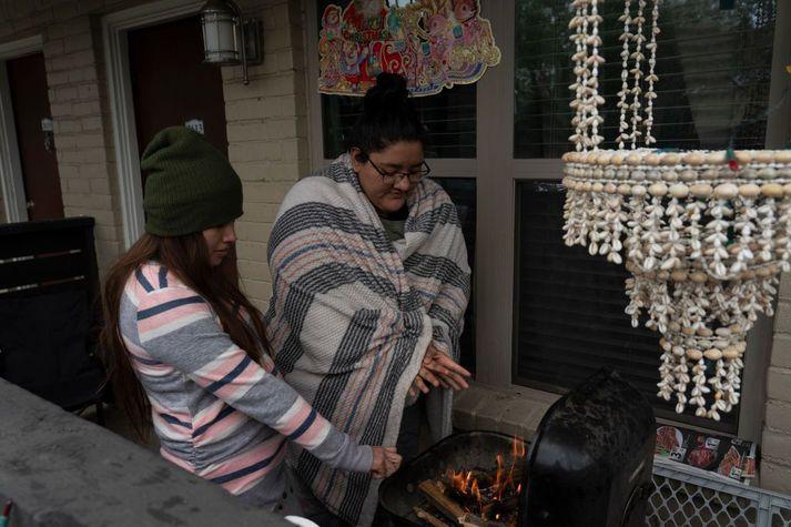 Karla Perez og Esperanza Gonzalez hlýja sér yfir grillinu á heimili sínu í Texas sem er án rafmagns vegna kulda og snjóa.