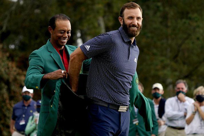 Tiger Woods klæðir Dustin Johnson hér í græna jakann fræga eftir sigurinn á Mastersmótinu í gær.
