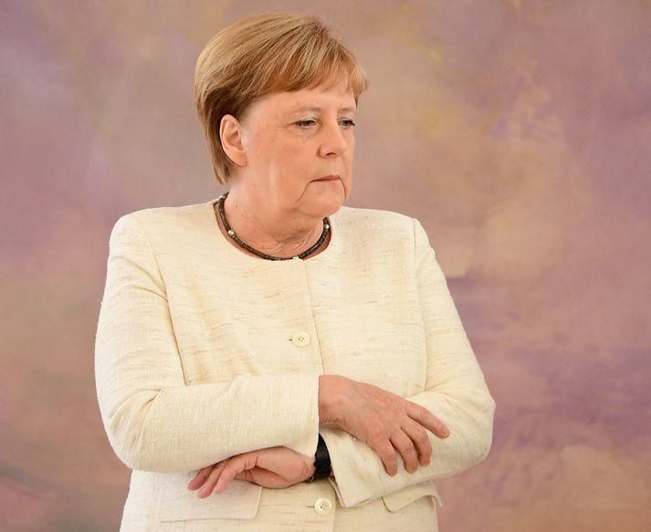 Angela Merkel sést hér halda handleggjunum þétt að sér, að því er virðist til að hafa heimil á skjálftanum.