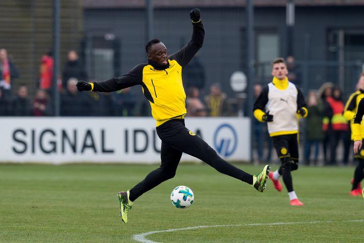 Usain Bolt reynir að sparka í bolta.