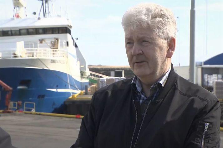 Gunnar Tómasson, framkvæmdastjóri Þorbjarnar hf. Fyrir aftan er verið að landa úr togaranum Tómasi Þorvaldssyni GK-10.