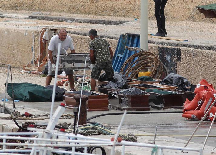 Líkkistur flóttafólks á hafnarbakkanum á ítölsku eyjunni Lampedusa í dag.