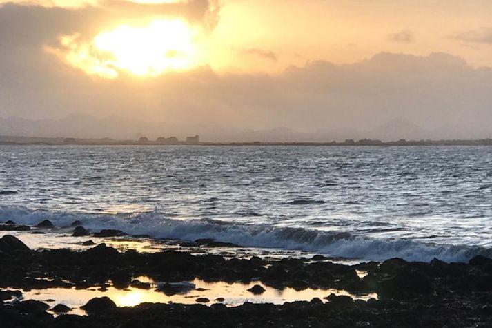 Skíma vetrarsólar yfir Bessastöðum og Reykjanesfjallgarði í dag, séð frá Ægissíðu í vesturbæ Reykjavíkur.