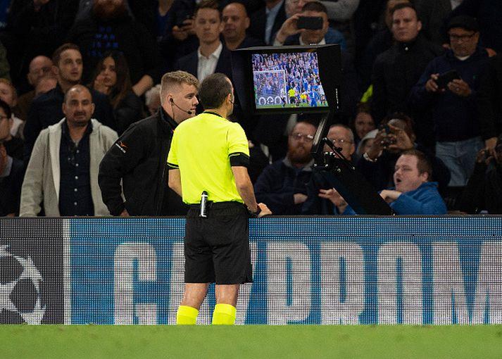 Cuneyt Cakir skoðar atvik í leik Chelsea og Valencia í Meistaradeildinni.