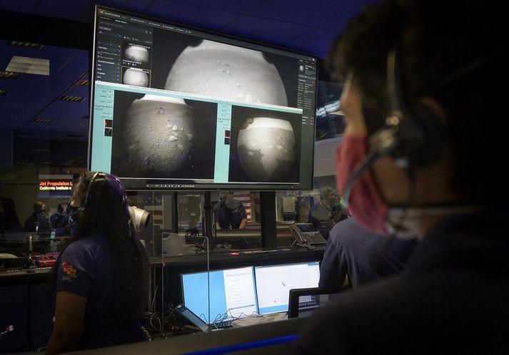 Starfsmenn NASA virða fyrstu myndir Perseverance frá Mars fyrir sér.