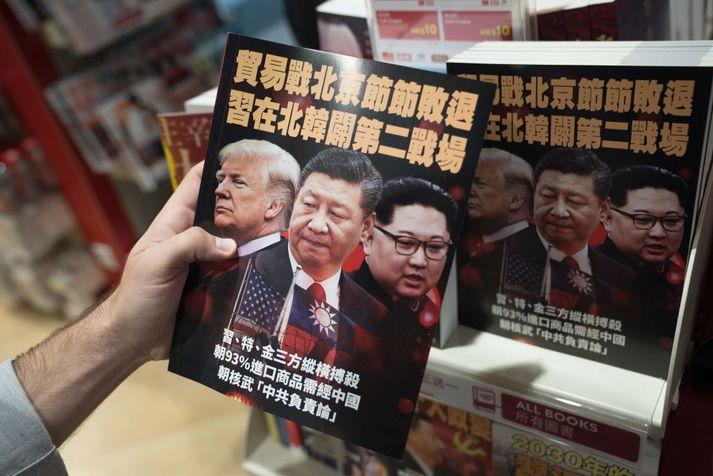 Donald Trump, forseti Bandaríkjanna, Xi Jinping, forseti Kína, og Kim Jong-un, æðsti leiðtogi Norður-Kóreu á forsíðu bókar sem var til sölu á flugvellinum í Hong Kong.