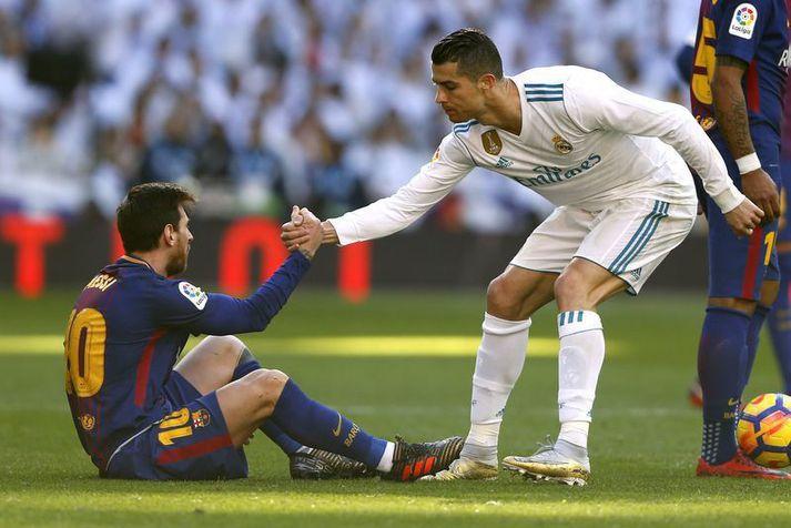 Cristiano Ronaldo hjálpar Lionel Messi á fætur þegar þeir mættust með Real Madrid og Barcelona í desember 2017.