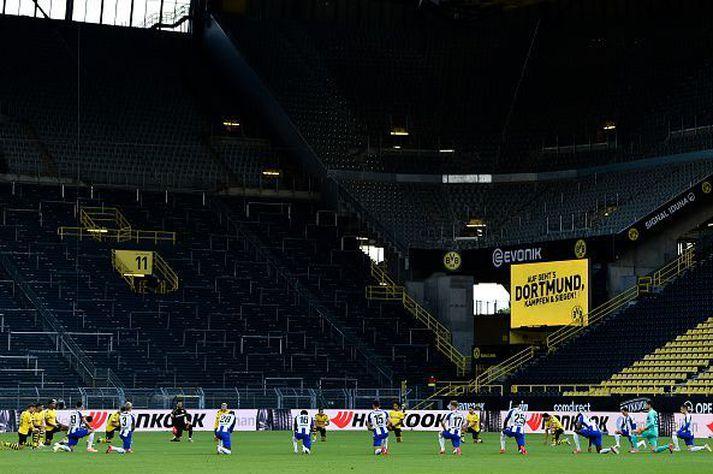 Mínútu þögn á hnjánum fyrir leik Dortmund og Herthu Berlínar í dag.