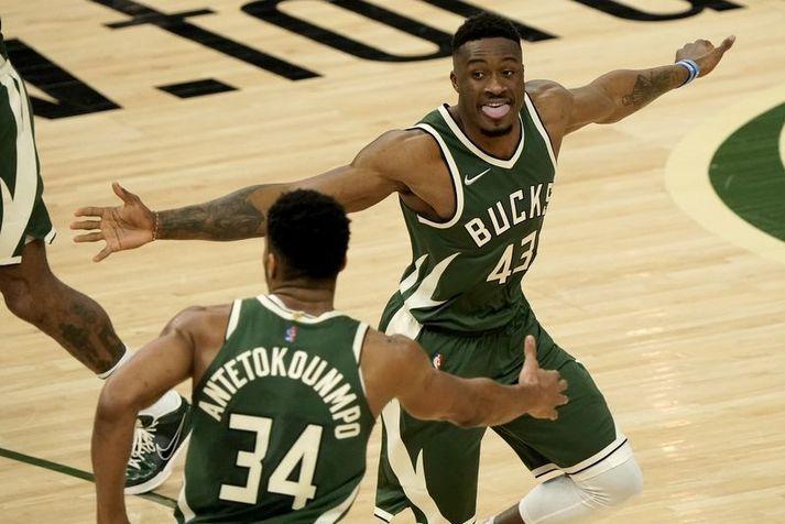 Bræðurnir Giannis Antetokounmpo og Thanasis Antetokounmpo fagna saman góðri körfu hjá Milwaukee Bucks í nótt.