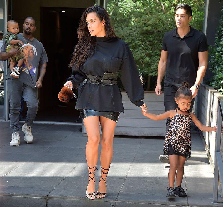 Kim og North í New York í ágúst í fyrra. Í baksýn sést Kanye West, eiginmaður Kim og faðir North, sem heldur á Saint, syni hans og Kim.