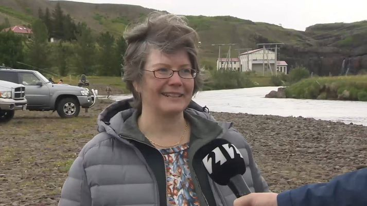 Ragnhildur Helga Jónsdóttir, formaður Veiðifélags Andakílsár. Stöðvarhús Andakílsárvirkjunar í baksýn.