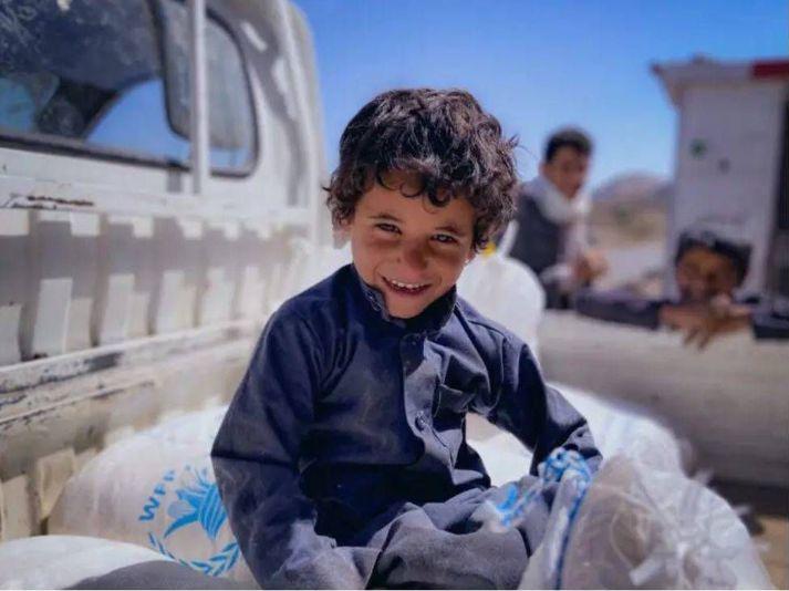 Omar, fjögurra ára, situr á hveitsekkjum WFP í Khawlan i Jemen.