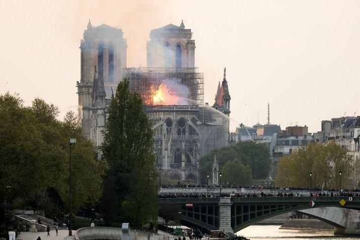 Slökkviliðsmenn slökkva eldinn með vatnsslöngum í Notre Dame í gær.