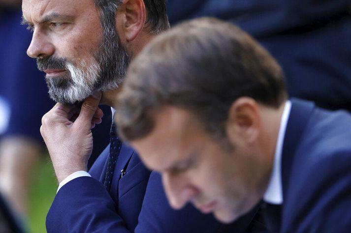 Emmanuel Macron Frakklandsforseti í forgrunni og Edouard Philippe fráfarandi forsætisráðherra strýkur í gegnum skeggið.