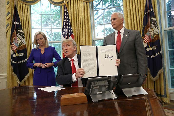 Donald Trump við undirritun tilskipunarinnar í kvöld, ásamt Kristjen Nielsen heimavarnaráðherra Bandaríkjanna og Mike Pence varaforseta.