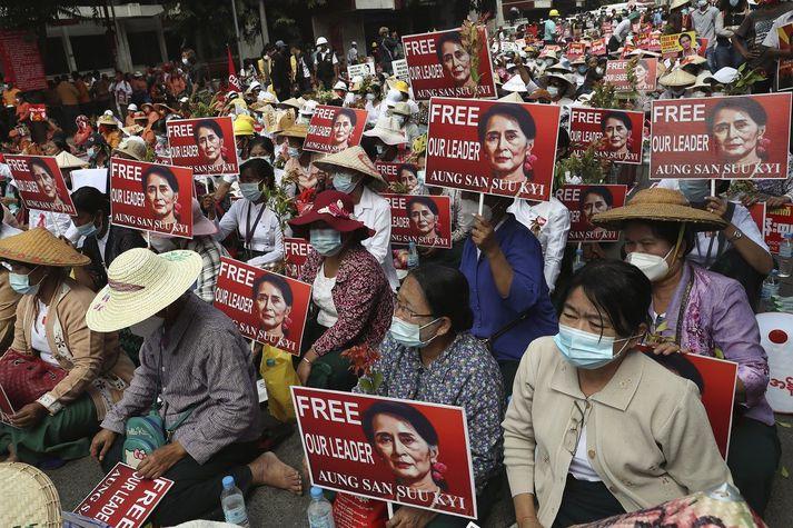 Mótmælendur halda uppi myndum af Aung San Suu Kyi en hún og margir úr flokki hennar, sem vann stóran sigur í kosningum síðasta árs, eru nú haldið í stofufangelsi af hernum.