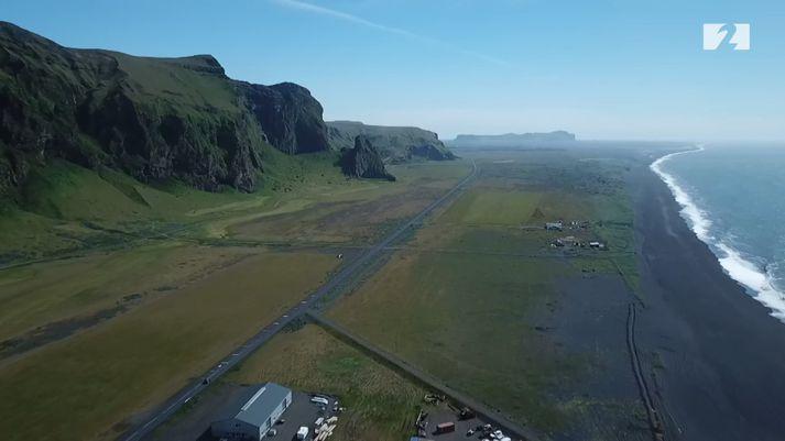 Víkurklettur sést fyrir miðri mynd en út frá honum verður varnargarðurinn lagður. Austustu húsin í Vík sjást neðst.
