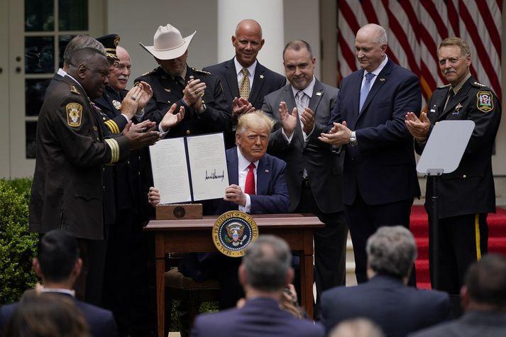 Donald Trump skrifaði undir tilskipunina umkringdur löggæsluaðilum.
