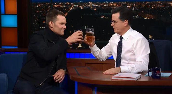 Brady og Colbert skála. Tveimur sekúndum síðar var Brady búinn með glasið.