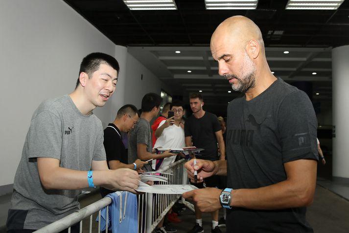 Pep Guardiola gefur hér eiginhandaráritun í Kína.