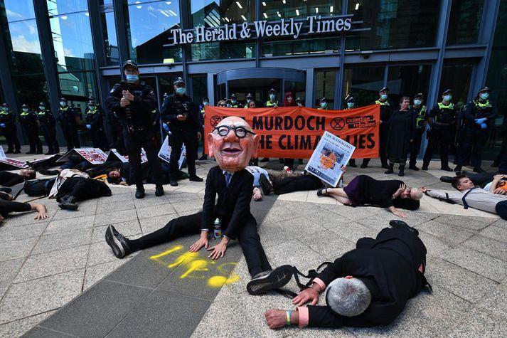 Loftslagsaðgerðasinni með grímu sem á að líkjast Rupert Murdoch mótmælir fyrir utan skrifstofur útgáfufélagsins The Herald and Weekly Times, eins fyrirtækja News Corp, í Melbourne í mars.