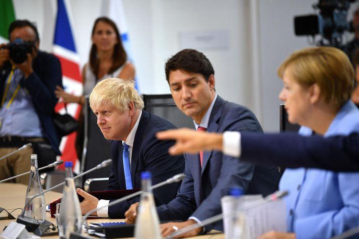 Johnson og Merkel með Justin Trudeau, forsætisráðherra Kanada, á milli sín á G7-fundi fyrr á þessu ári.