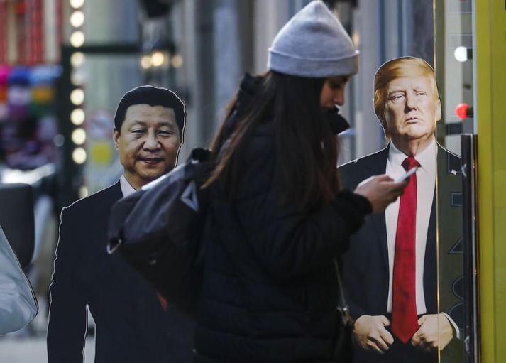 Kona stendur við útskornar myndir af Xi Jinping, forseta Kína, og Donald Trump Bandaríkjaforseta í Moskvu. Samskipti Kína og Bandaríkin hafa farið versnandi í tíð Trump sem hóf viðskiptastríð gegn stjórnvöldum í Beijing.