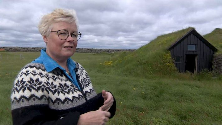 Lilja Magnúsdóttir við bæinn að Hnausum í Meðallandi. Fyrir aftan má sjá hvar hraunið stöðvaðist árið 1783.