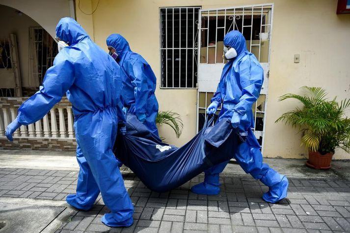 Lögreglumenn í hlífðarbúningi flytja lík manneskju sem lést úr Covid-19 í borginni Guayaquil í Ekvador 17. apríl.
