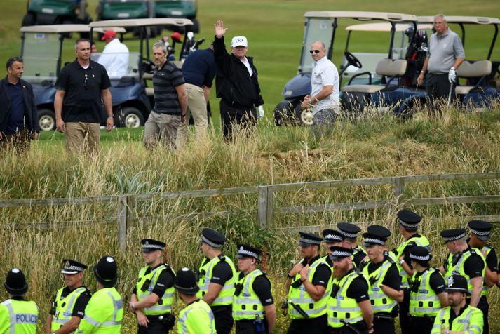 Fjölmennt lögreglulið stóð vaktina við Turnberry-golfvöll Trumps í dag. Forsetinn sést hér veifa mótmælendum, sem tóku illa í kveðjuna.