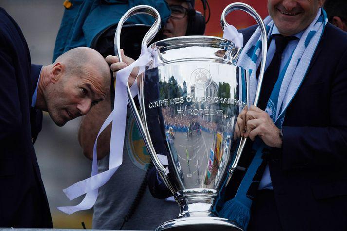 Zinedine Zidane skoðar bikarinn sem hann hefur unnið einu sinni sem leikmaður og þrisvar sinnum sem stjóri.