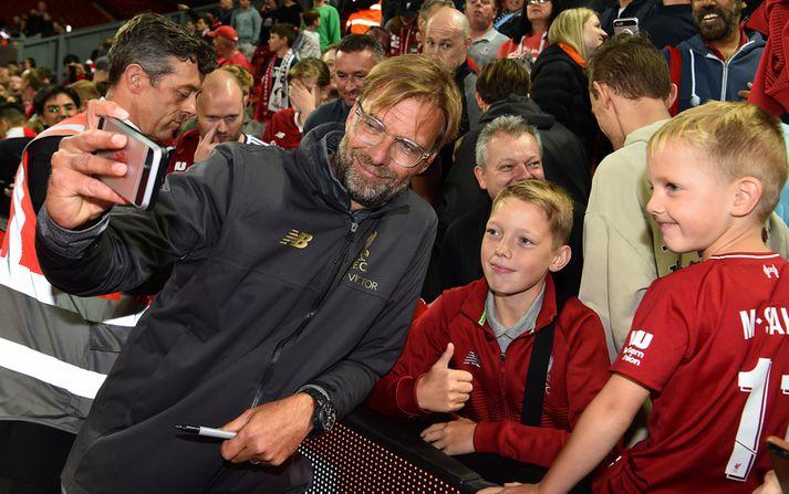 Jürgen Klopp afslappaður með ungum stuðningsmanni Liverpool.