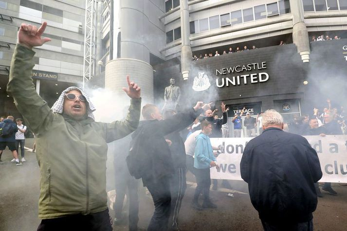 Stuðningsmenn Newcastle United fagna yfirtökunni fyrir framan St. James leikvanginn á táknrænan hátt.