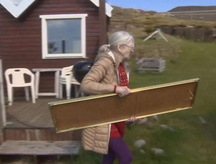 Stefanía Haraldsdóttir ber út spegil úr bústað á jörðinni Ísólfsskála í dag.