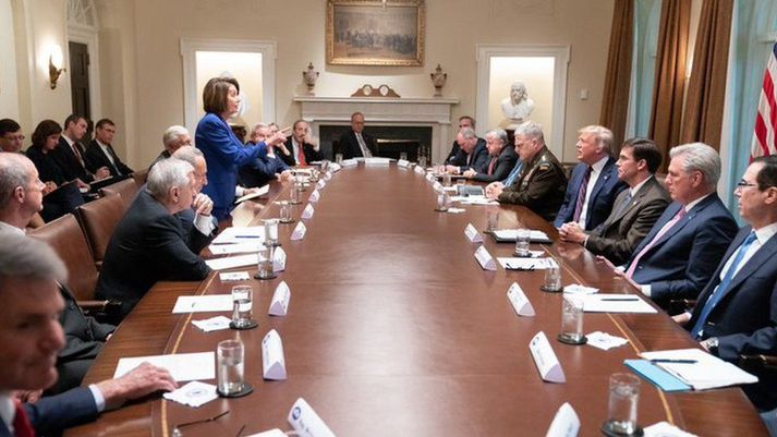Nancy Pelosi stendur við borðið á fundi Demókrata Donald Trump.
