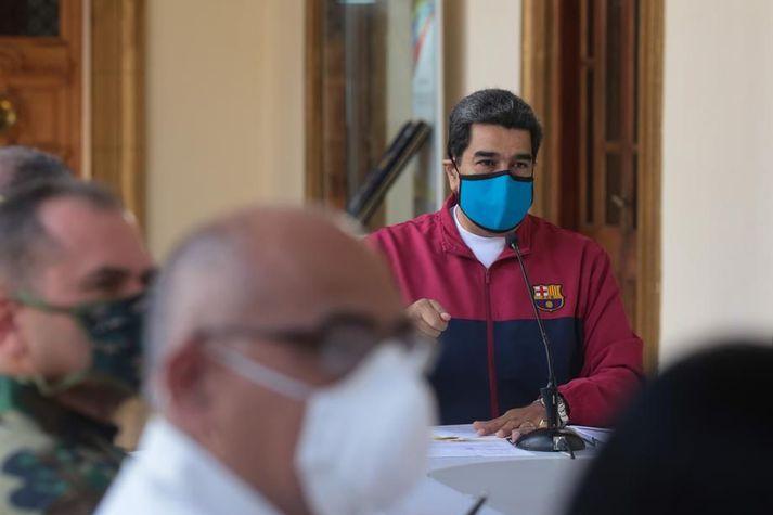 Maduro forseti með grímu fyrir vitum sér á fundi um kórónuveirufaraldurinn í Miraflores-forsetahöllinni í Caracas á sunnudag. Hann verður ákærður fyrir fíkniefnabrot í Bandaríkjunum.