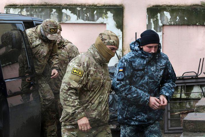 Rússneskir hermenn fylgja úkraínskum sjóliða inn í dómhús í borginni Símferopol á Krímskaga.