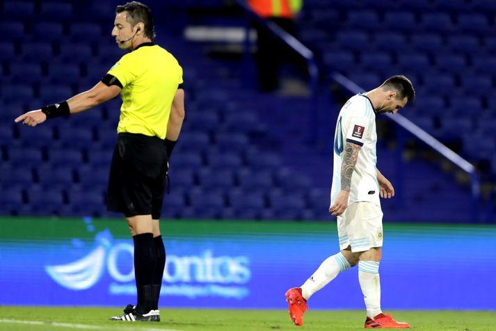 Lionel Messi gengur niðurlútur framhjá brasiliska dómaranum Raphael Claus sem hefur dæmt markið hans af.