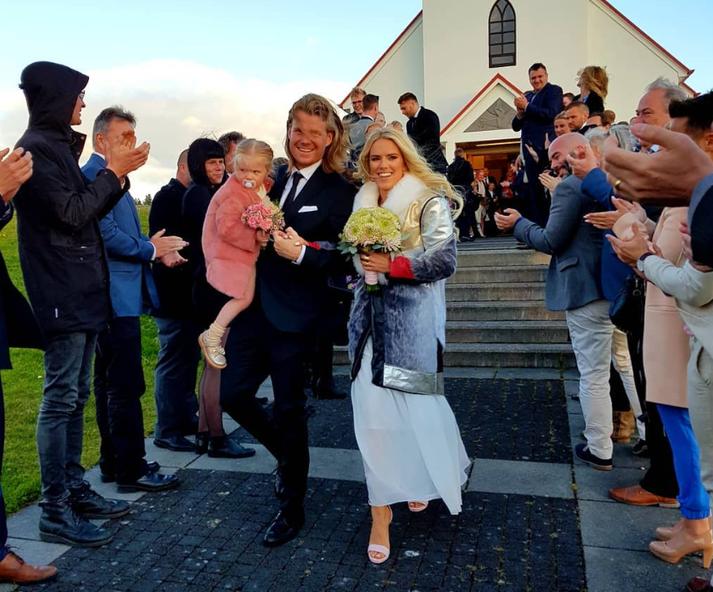 Davíð og Jóhanna Guðrún ganga alsæl niður kirkjutröppurnar ásamt dóttur þeirra eftir athöfnina í Garðakirkju í dag.
