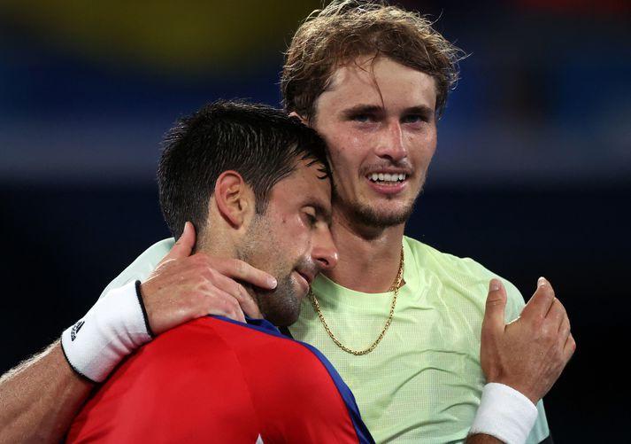 Novak Djokovic og Alexander Zverev fallast í faðma eftir undanúrslitaleikinn í dag.