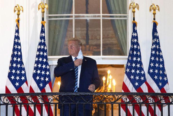 Trump sést hér koma fram á svalir Hvíta hússins eftir að hann útskrifaðist af spítala og taka af sér andlitsgrímu.