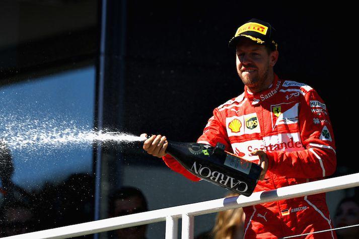 Sebastian Vettel fagnaði með því að frussa freyðivíni eftir keppnina.