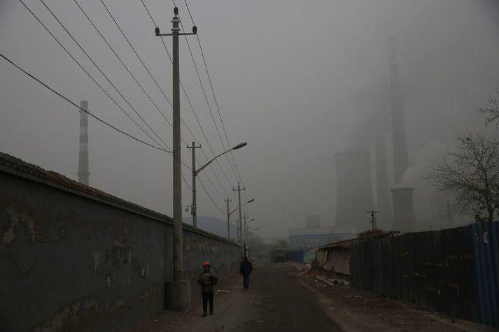 Kolaorkuver í Peking sést naumlega í gegnum mengunarmóðu. Helmingur allra kolaorkuvera heimsins eru í Kína.