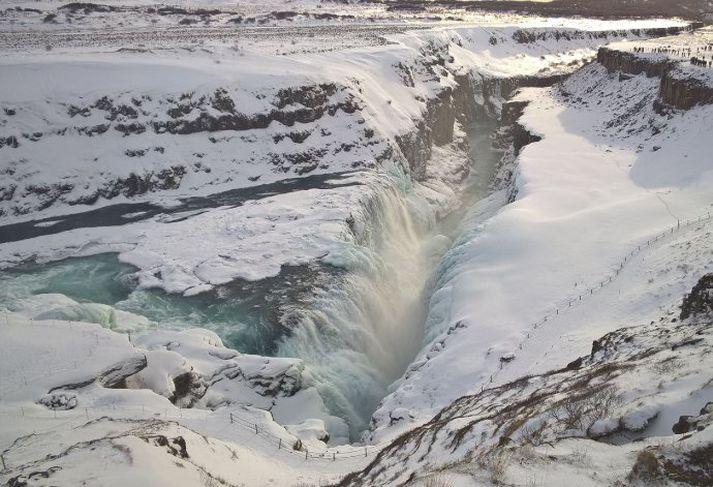 Flughált er við malargöngustíg niður að fossinum vegna vatnsúða sem breytist í ísbrynju.