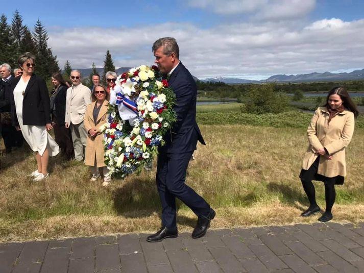 Bjarni Benediktsson ber blómsveig að minnisvarða um þáverandi forsætisráðherra og nafna, eiginkonu hans og barnabarn.